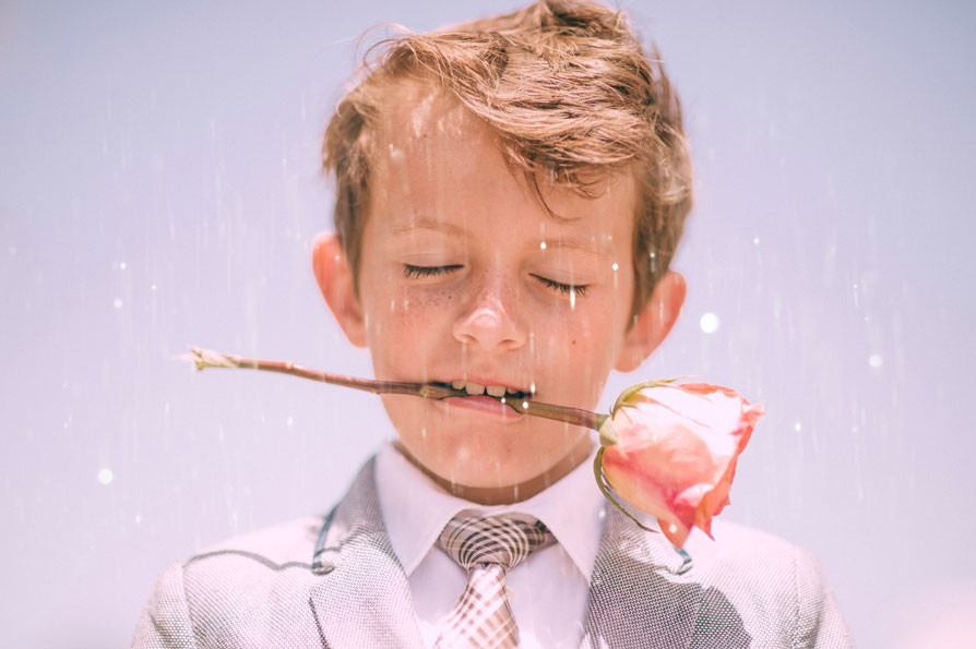 Boy with a rose in his mouth